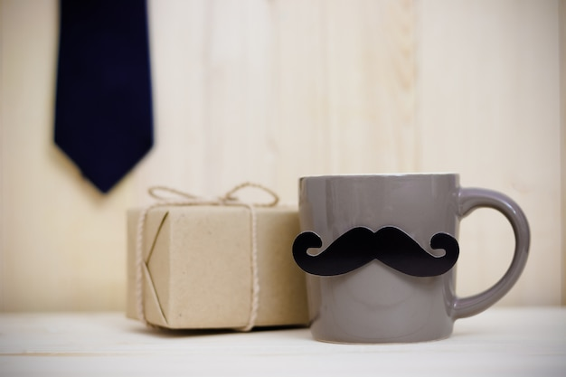 Tie, gift box, paper mustache, coffee cup on wooden background with copy space. happy father's day.