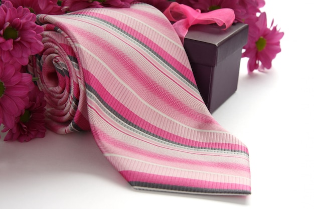 Tie and gift box with flowers over white