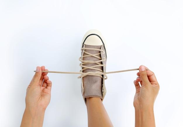 白い背景に彼女の靴のキャンバススニーカーを結ぶ