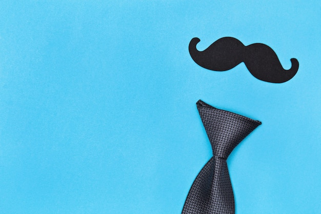 Tie and mustache on blue surface