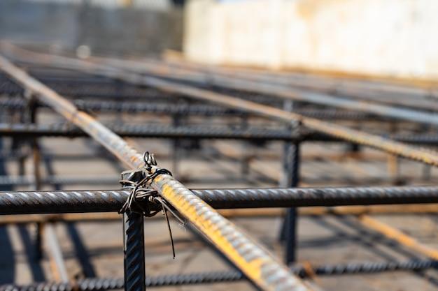 Обвяжите каркас арматурной балки на строительной площадке. стальной арматурный стержень для железобетона.