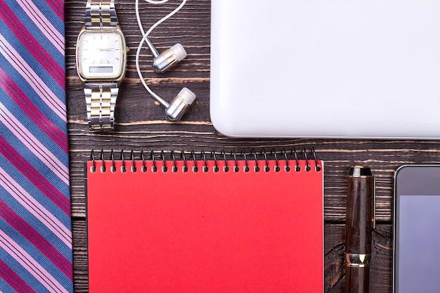 Галстук, часы и блокнот. наушники, планшет и смартфон. завершите свой корпоративный образ.