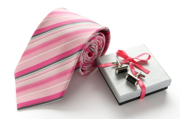 Tie with cuff links and gift box on white background