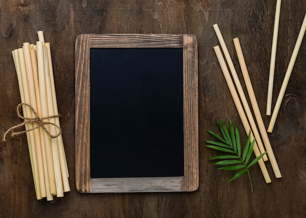 Tied bamboo organic straws copy space blackboard frame