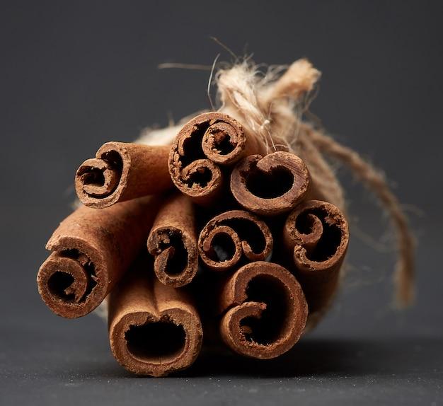 Tied bunch of brown cinnamon sticks on a dark background