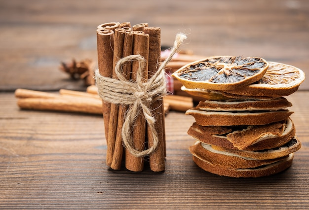 木製の背景に茶色のシナモンスティックの束を結んで、クローズアップ