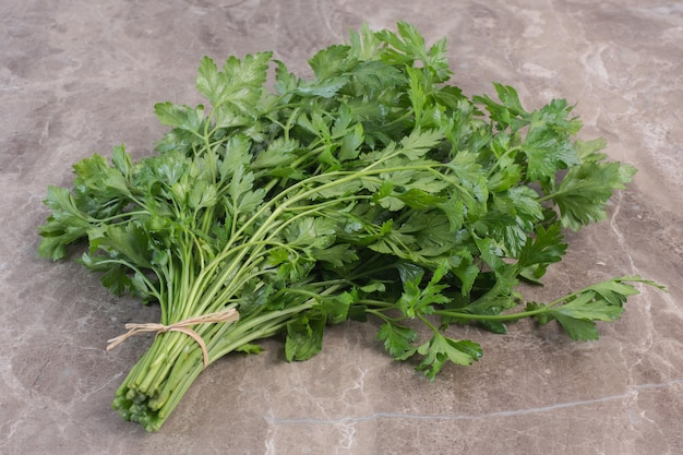 Tied bundle of parsley on marble surface