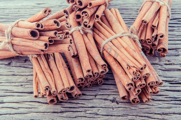 Tied cinnamon stick with selective focus on old wooden background .