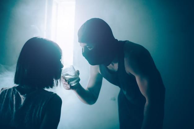 Связанная девушка склоняется к стакану с водой, который держит парень в маске. на нем черная маска. мужчина смотрит на нее. они в темной комнате.