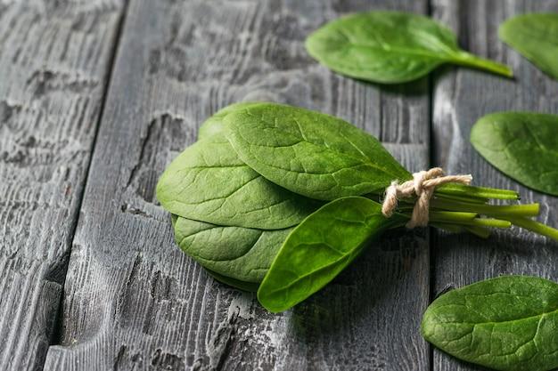검은 나무 테이블에 시금치 잎의 무리에 묶여 있습니다. 건강을 위한 음식. 채식주의 자 음식.