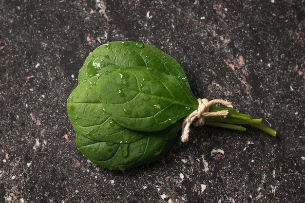 검은 돌 배경에 젖은 시금치 잎 묶음에 묶여 있습니다. 건강을 위한 음식. 채식주의 자 음식. 정상에서 본 모습.