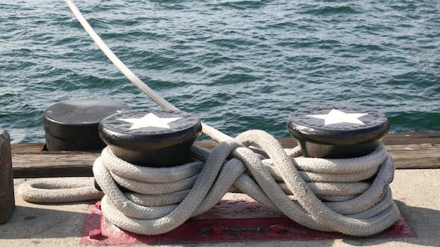금속 기둥, 샌디에고 항구에 묶인 된 밧줄 매듭. 해상 선박 정박, 해군 함대, 미국 국기.