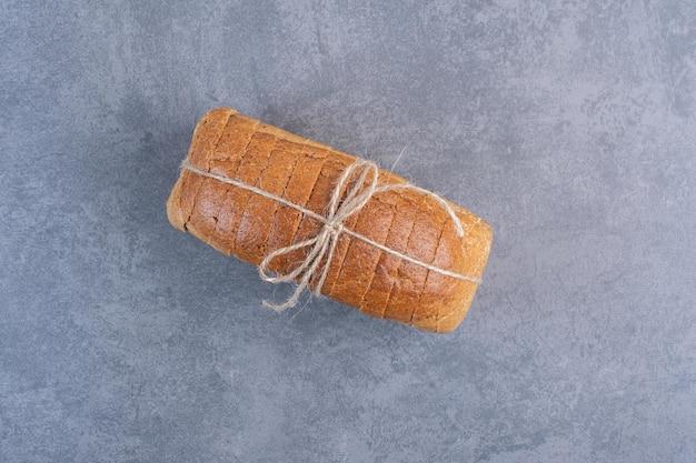 대리석 배경에 얇게 썬 빵의 묶인 된 블록. 고품질 사진