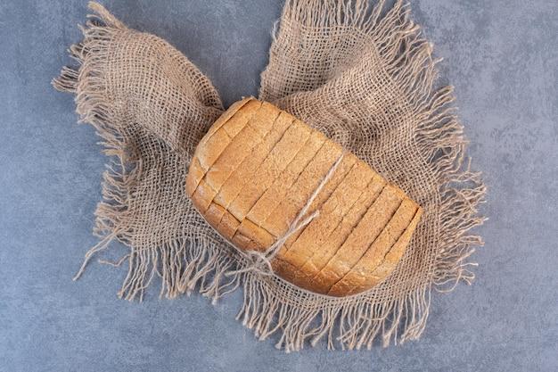 Blocco legato di pane a fette su un pezzo di stoffa su fondo marmo. foto di alta qualità