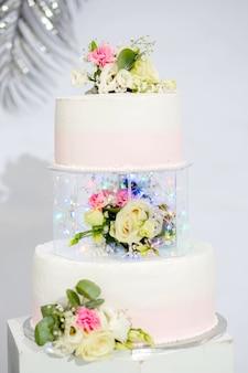 결혼식이나 생일을 위한 계층 케이크. 꽃으로 장식된 아름다운 흰색과 분홍색 축제 케이크
