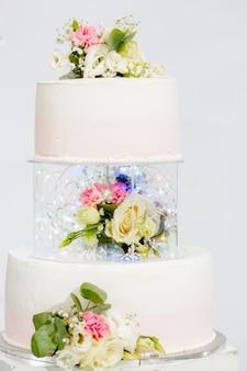 결혼식이나 생일을위한 계층 케이크. 꽃으로 장식 된 아름다운 흰색과 분홍색 축제 케이크.
