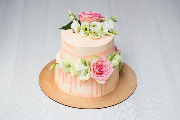 Многоярусный торт со свежими цветами и макарунами