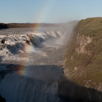 Tiered waterfall with grassed cliff and rainbow