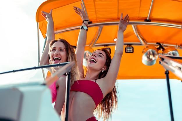 우정의 유대. 요트 갑판에서 춤을 추며 인생을 즐기는 두 명의 좋은 젊은 여자 친구