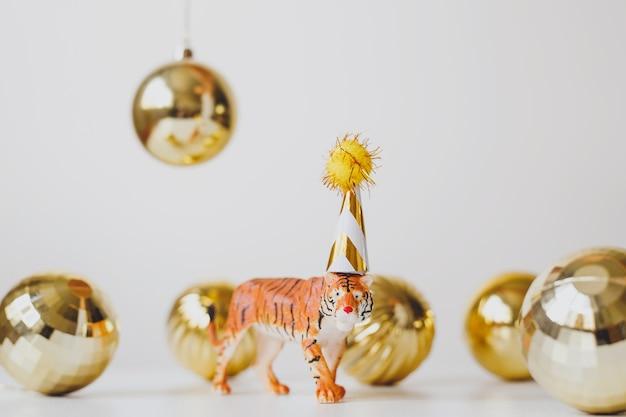 Фигурка тигра в кепке с золотыми елочными шарами символ китайского нового 2022 года