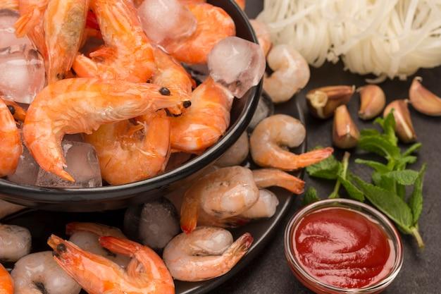 Тигровые креветки и креветки в черной тарелке со льдом. томатный соус, мята, чеснок.