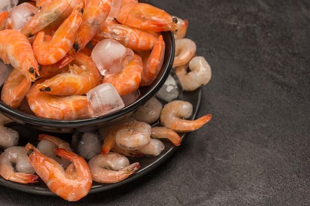 Тигровые креветки и креветки в черной тарелке со льдом.