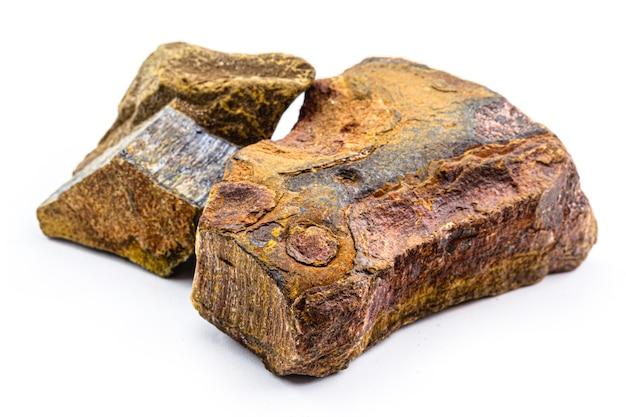 タイガーズアイの石、天然、カットなし、装飾用および難解な鉱石、鮮やかな色の珪化クロシドライト Premium写真