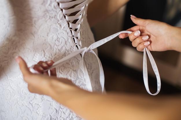 花嫁のウェディングドレスを締めます