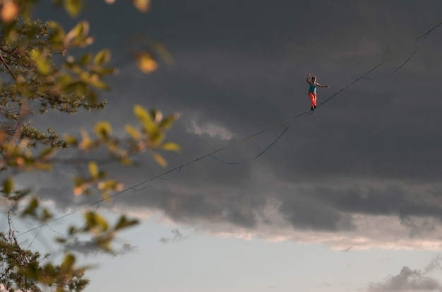 A tightrope walker walks along the highline against the backdrop of a dramatic sky