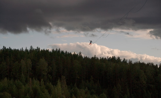 A tightrope walker walks along the highline above the forest