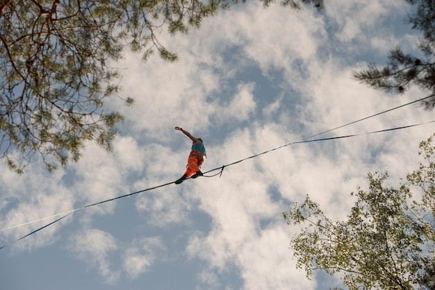 A tightrope walker walks along the highline over the trees