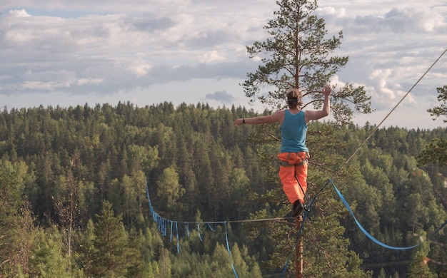 A tightrope walker walks along a long highline above the forest. back view