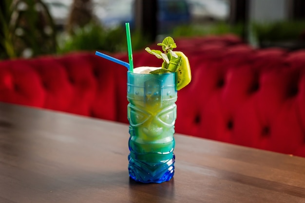 A tiki style cocktail in a colorful blue glass, kiwi and mint garnish at the bar