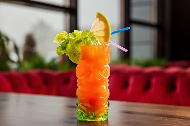 A tiki style orange cocktail in a colorful glass, celery and lemon garnish, at the bar