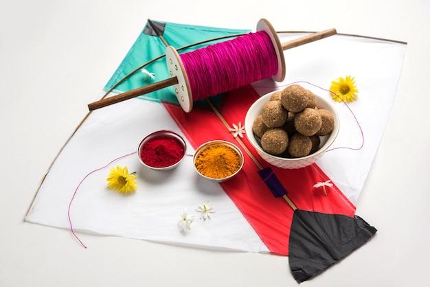 Til gul or sweet sesame laddu with fikri 및 kite with haldi kumkum for makar sankranti 축제를 위한 변덕스러운 배경, 선택적 초점