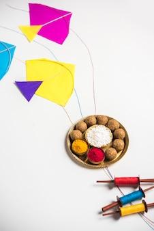 Til gul 또는 sweet sesame laddu와 miniature fikri 및 kite 모델이 포함된 haldi kumkum 및 makar sankranti 축제를 위한 설탕 결정이 변덕스러운 배경, 선택적 초점