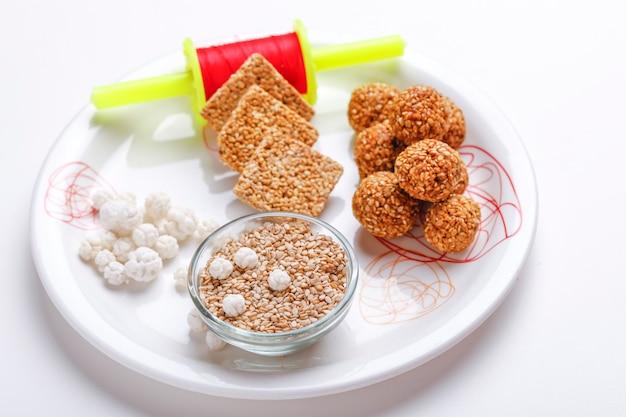 Til gul or sweet sesame laddu in plate with fikri for indian festival makar sankranti
