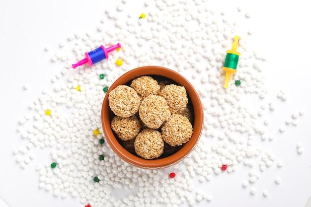 Til gul or sweet sesame laddu with fikri for indian festival makar sankranti