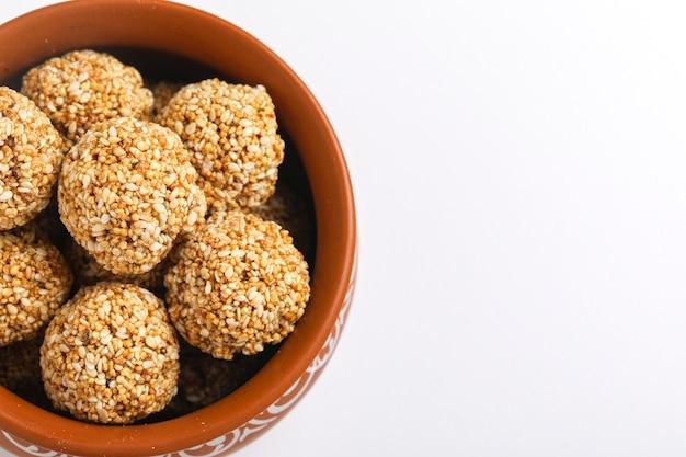 Til gul or sweet sesame seed ball or laddu with fikri for indian festival makar sankranti
