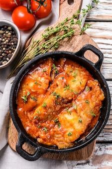 鍋でトマトで焼いたティラピアの魚。白い木製の背景。上面図