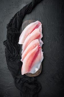 Отрезки мяса филе рыбы тилапии, на черном столе, вид сверху