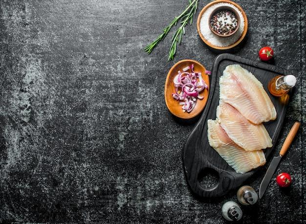 黒の素朴なテーブルのボウルにスパイスとタマネギのスライスとティラピアの魚の切り身