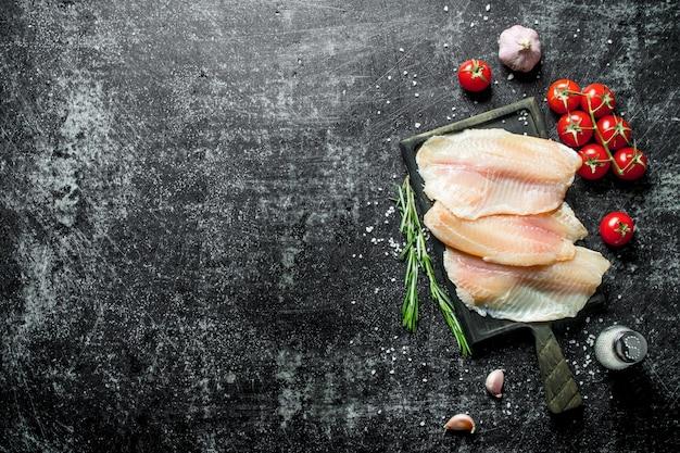 Филе рыбы тилапии с помидорами на веточке, розмарином, чесноком и солью.