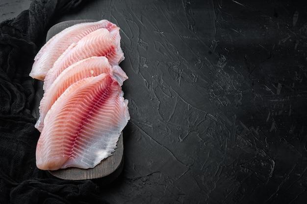 Рыба тилапия, мясо без кожи, на черном столе