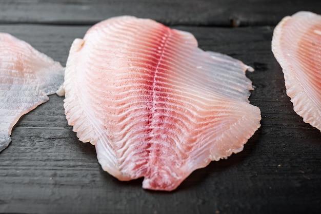 ティラピアの魚、皮のない肉、黒い木製のテーブル