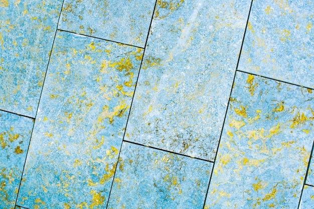 タイル、大理石、コンクリートの熟成テクスチャ。古い、ヴィンテージブルー、フォーチュナゴールドの背景。ざらつきやひび割れのある金。