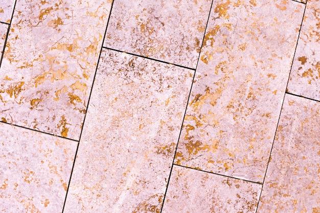 タイル、大理石、コンクリートの熟成テクスチャ。古い、ヴィンテージピンク、フォルトゥーナゴールドの背景。ざらつきやひび割れのある金。