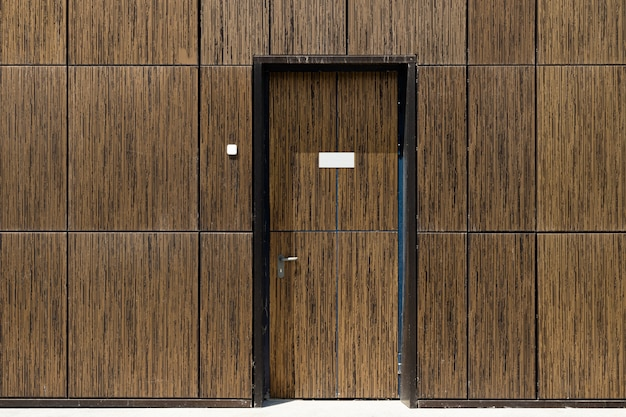 Tiled brown wall with built-in camouflaged door, front view. copyspace on door.