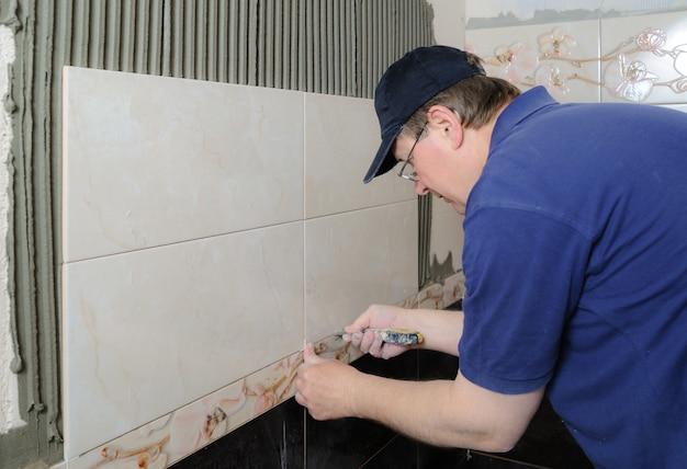 Плиточник укладывает керамическую плитку