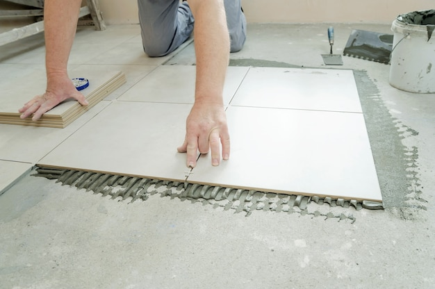 A tiler is putting a spacer between a ceramic tiles.
